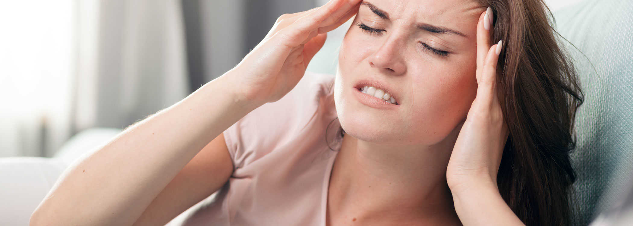 Woman appearing to have a headache due to Bruxism.