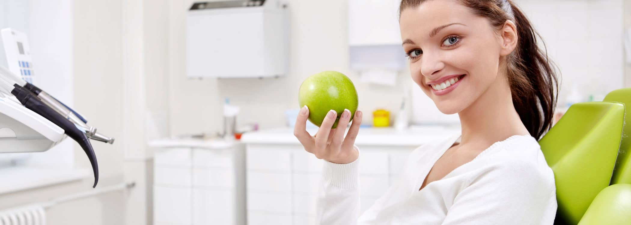 Dental patient smiling and holding a green apple.