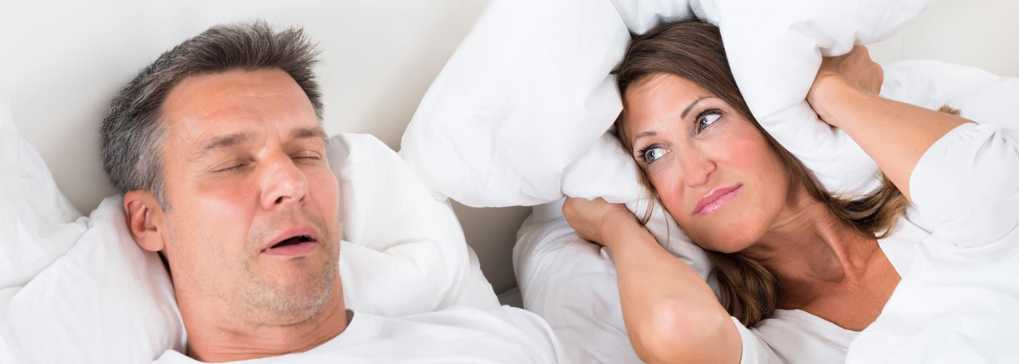Snoring - woman holding pillows over her ears as male snores.